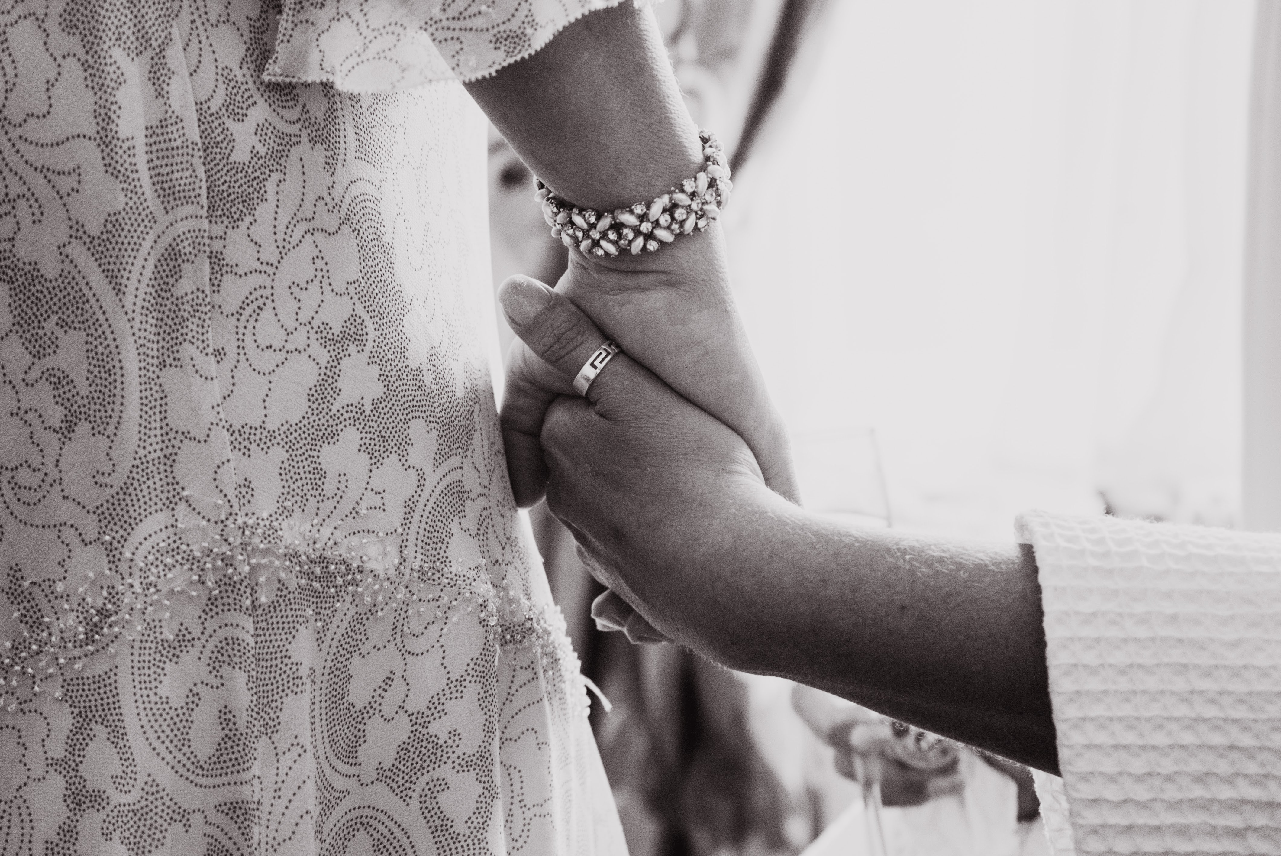 mum holding hands with bride