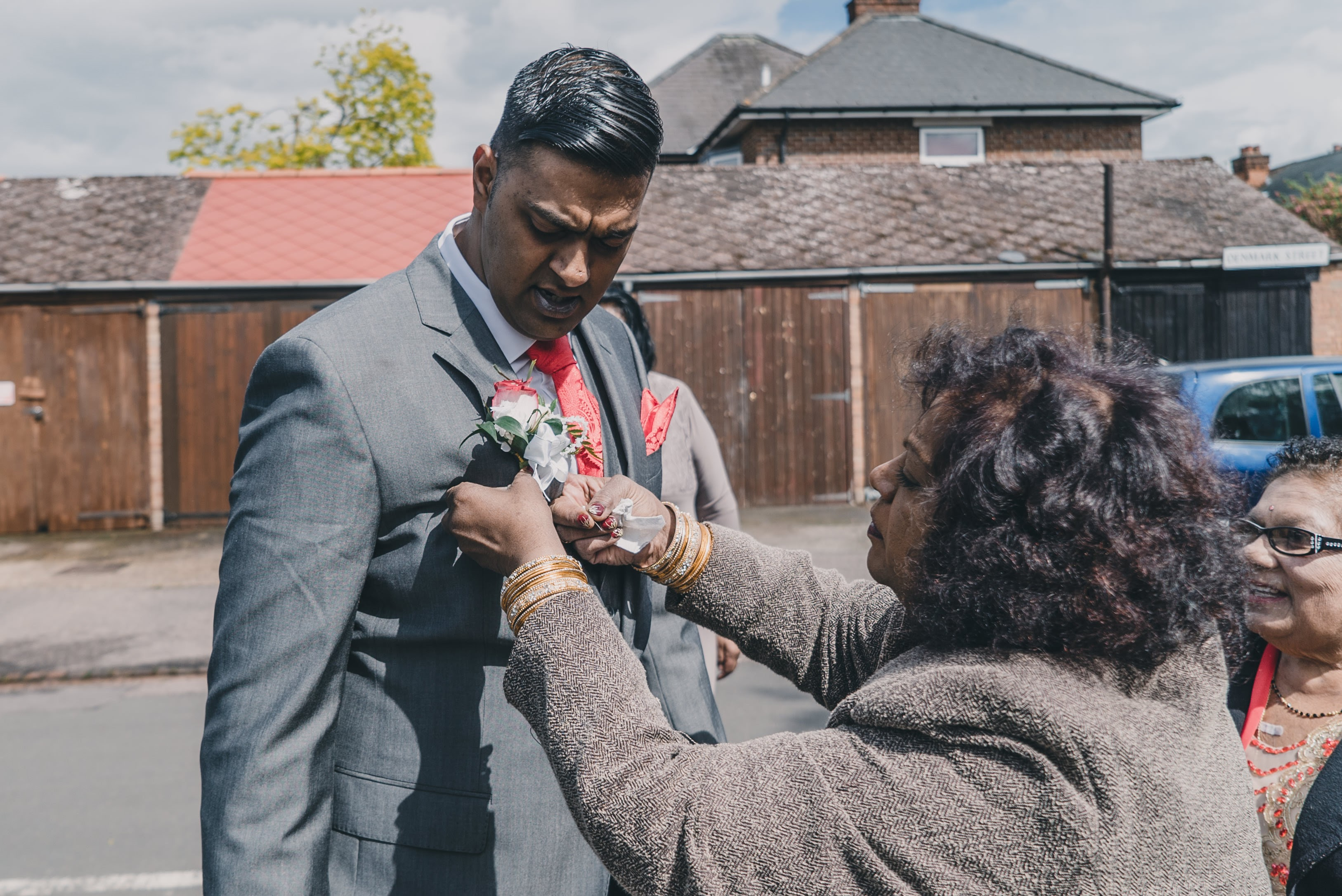 grooms mother putting flower on groom